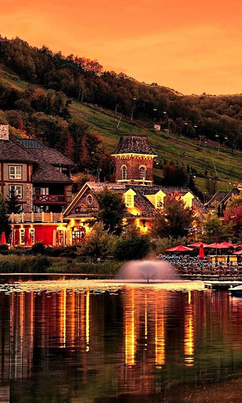 Картинка вечер, фонтан, озеро, гора, склон, пруд, дома, закат 480x800 на телефон